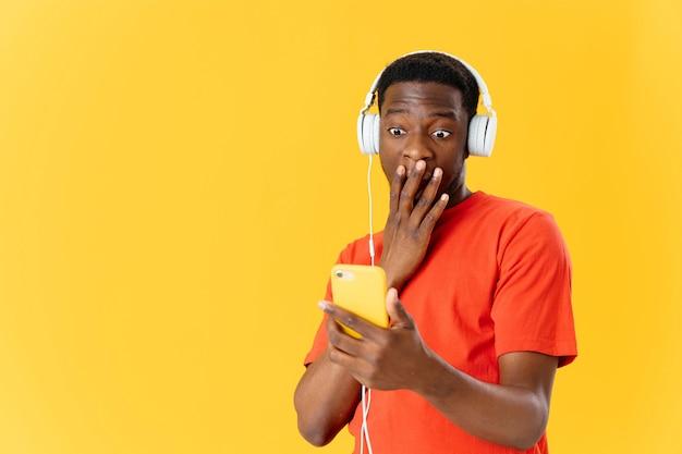 Homem africano surpreso com fones de ouvido, tecnologia e música