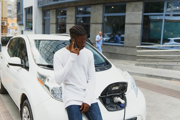 Homem africano usa telefone inteligente enquanto espera e a fonte de alimentação se conecta a veículos elétricos para carregar a bateria do carro