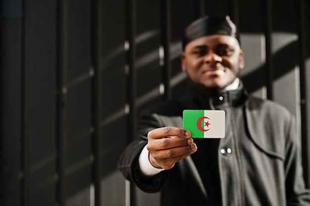 Homem africano usar durag preto segurar a bandeira da argélia na parede escura isolada mão.