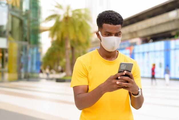 Homem africano vestindo camiseta amarela e máscara facial para se proteger do coronavírus covid-19 ao ar livre na cidade enquanto usa um telefone celular