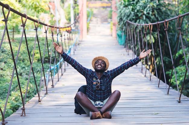Homem africano viajante sentado e sorrindo na ponte com óculos de sol