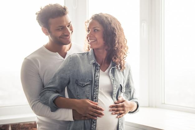 Homem afro abraça sua esposa grávida em casa
