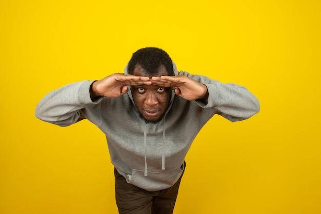 Homem afro-americano a espreitar, posando na parede amarela e azul.
