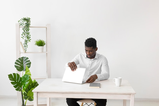 Homem afro-americano abrindo o laptop