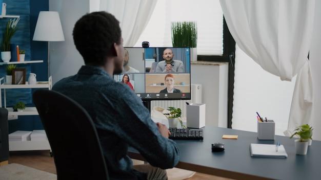 Homem afro-americano acenando para colegas conversando em uma chamada de conferência online pela internet