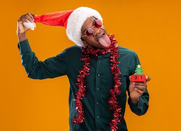 Homem afro-americano alegre com chapéu de papai noel com festão usando óculos escuros segurando cubos de brinquedo com a data de ano novo esticando a língua em pé sobre fundo laranja