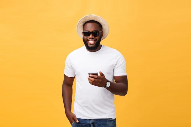 Homem afro-americano alegre na camisa branca usando o aplicativo de telefone celular.