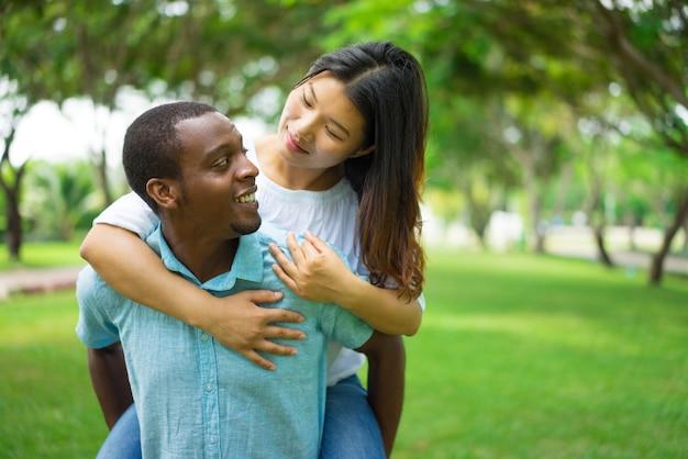 Homem afro-americano alegre que leva o reboque asiático da mulher.