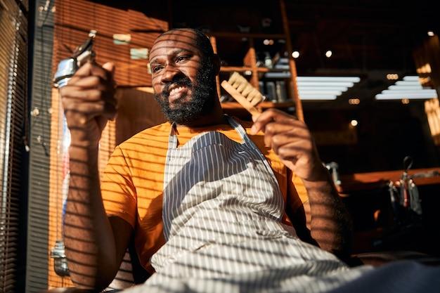 Homem afro-americano alegre segurando um aparador de cabelo e uma escova de barbeiro