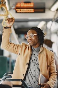Homem afro-americano andando no ônibus da cidade. cara com um casaco marrom. homem com caderno.