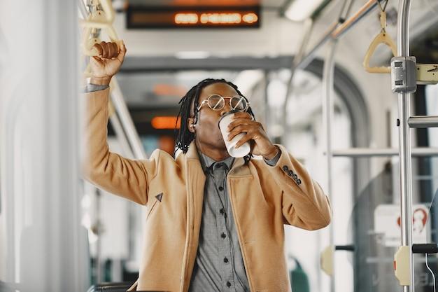 Homem afro-americano andando no ônibus da cidade. cara com um casaco marrom. homem com café.