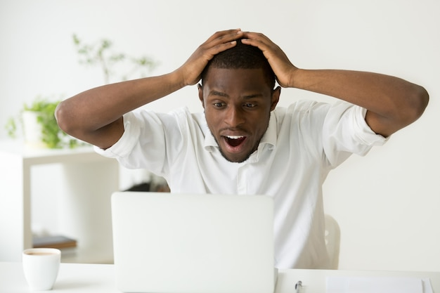 Homem afro-americano animado espantado surpreendido por boas notícias inesperadas on-line