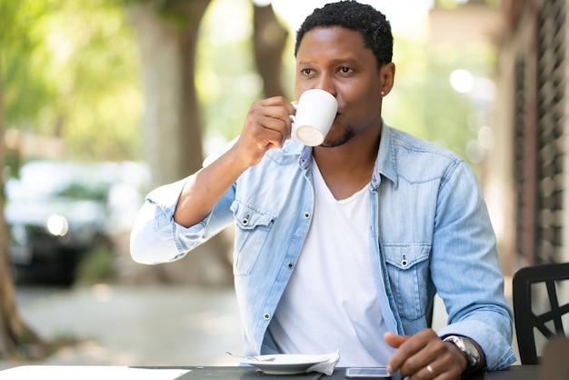 Homem afro-americano apreciando e bebendo um café enquanto está sentado em uma cafeteria ao ar livre
