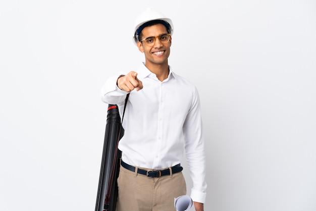 Homem afro-americano arquiteto com capacete e segurando plantas sobre parede branca isolada _ apontando frente com expressão feliz