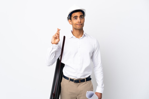 Homem afro-americano arquiteto com capacete e segurando plantas sobre parede branca isolada _ com dedos cruzando e desejando o melhor