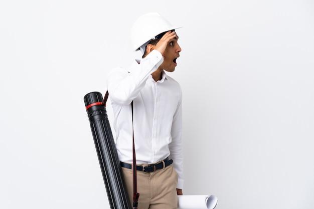 Homem afro-americano arquiteto com capacete e segurando plantas sobre parede branca isolada com expressão de surpresa enquanto olha de lado