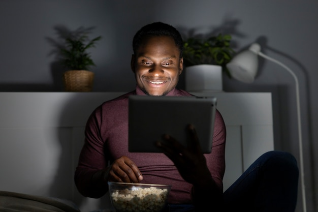Homem afro-americano assistindo netflix dentro de casa