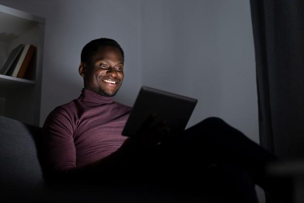 Homem afro-americano assistindo netflix sozinho em casa
