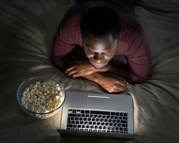 Homem afro-americano assistindo serviço de streaming em ambientes fechados