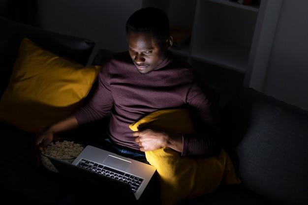 Homem afro-americano assistindo serviço de streaming em casa sozinho