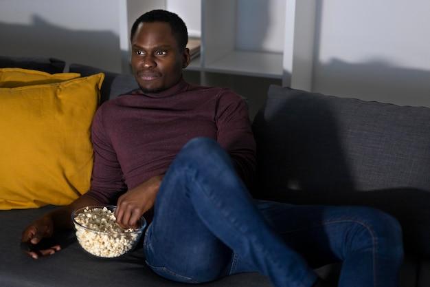 Homem afro-americano assistindo serviço de streaming em casa