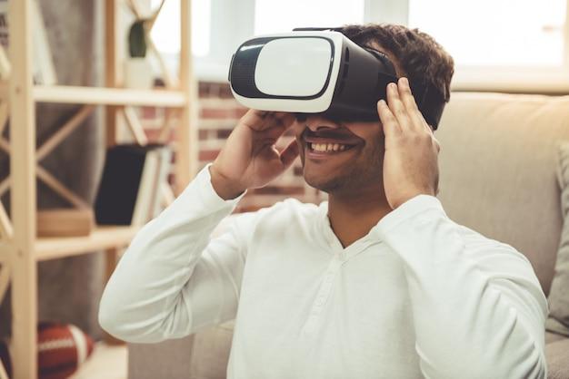 Homem afro-americano atraente está usando uma realidade virtual.