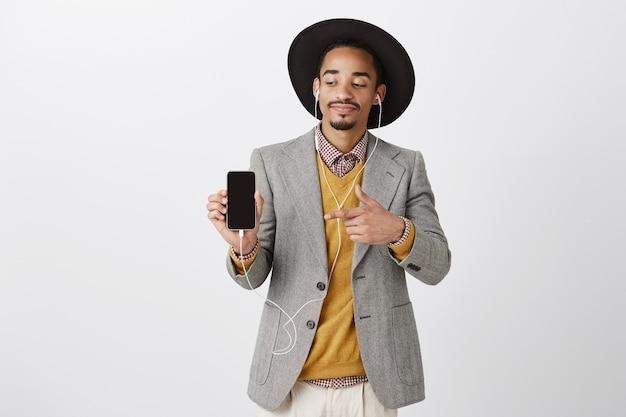 Homem afro-americano atraente satisfeito ouvindo música em fones de ouvido e apontando a tela do smartphone com dedo, mostrando o aplicativo