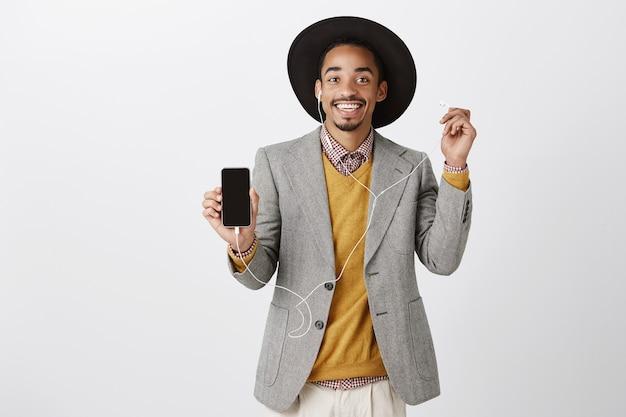 Homem afro-americano atraente satisfeito ouvindo música em fones de ouvido e mostrando a tela do celular, aplicativo