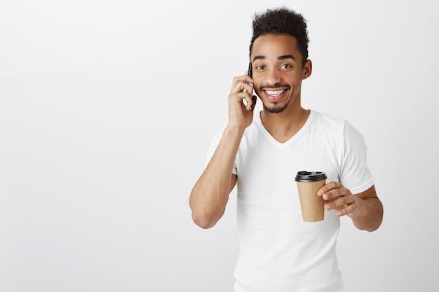 Homem afro-americano atraente sorridente falando ao telefone e bebendo café para viagem