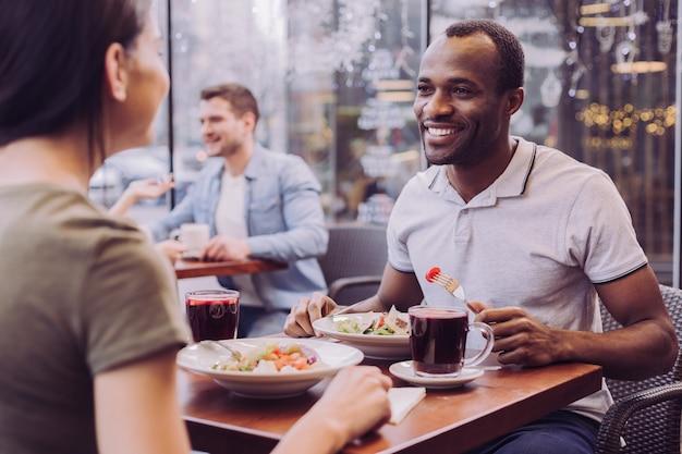 Homem afro-americano atraente sorrindo enquanto come salada e olha para uma mulher