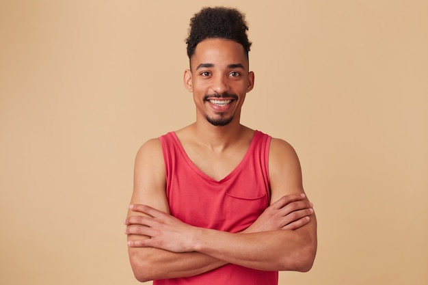 Homem afro-americano, barbudo cara feliz com penteado afro. usando um top vermelho. cruze as mãos em um baú isolado sobre uma parede bege pastel