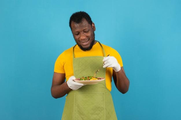 Homem afro-americano barbudo com comida em uma mão e um garfo na outra, em pé sobre a parede azul.