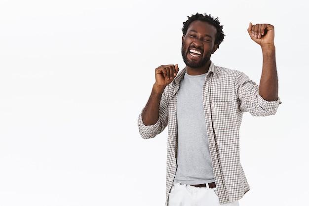 Homem afro-americano barbudo, feliz e entusiasmado e de boa aparência dançam a dança da sorte, celebrando o sucesso