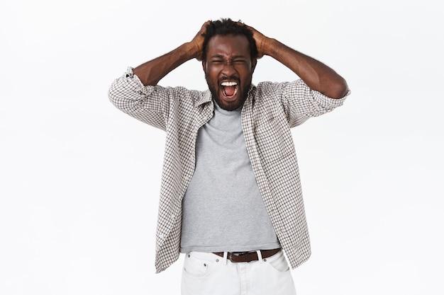 Homem afro-americano barbudo indignado e angustiado gritando de dor e perda, de mãos dadas na cabeça