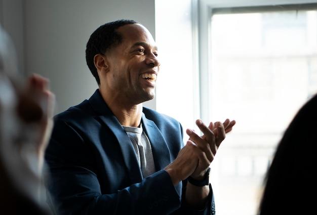 Homem afro-americano batendo palmas em um seminário