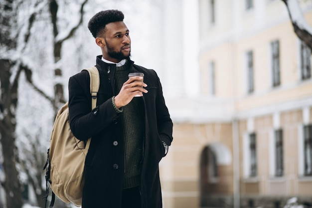 Homem afro-americano bebendo café lá fora no inverno