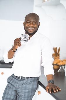Homem afro-americano bem sucedido jovem empresário fica com uma xícara na cozinha, ele está feliz e ...