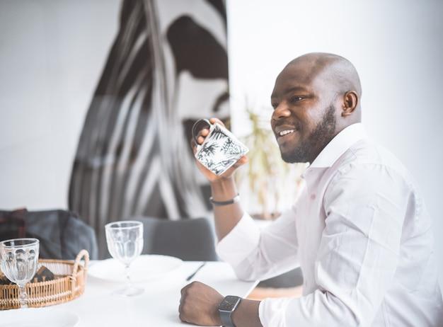 Homem afro-americano bem sucedido jovem empresário sorrindo enquanto está sentado no café da manhã em um luxo separado.