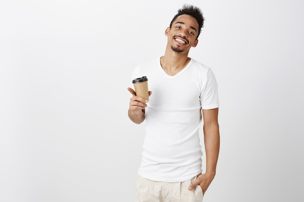 Homem afro-americano bonito carismático sorrindo e bebendo café