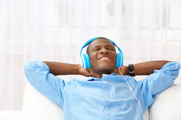 Homem afro-americano bonito com fones de ouvido deitado no sofá close-up