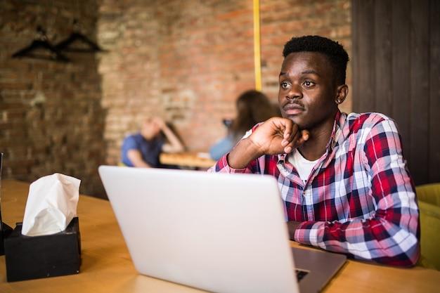 Homem afro-americano bonito com roupas casuais, segurando uma xícara de café e usando o laptop.