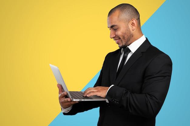 Homem afro-americano bonito com um laptop