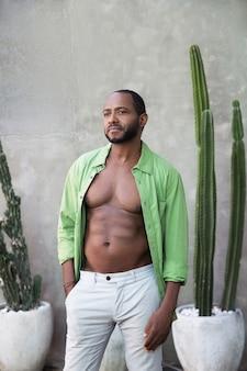 Homem afro-americano bonito e alegre com uma camisa verde aberta com cactos nos trópicos
