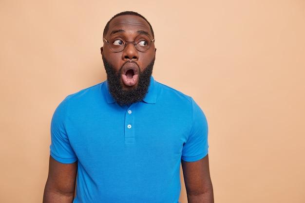 Homem afro-americano bonito e barbudo fica surpreso ao ouvir notícias inacreditáveis, fica de queixo caído e vê algo de tirar o fôlego em uma parede bege
