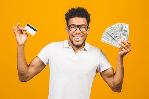 Homem afro-americano bonito e barbudo segurando uma pilha de dinheiro e um cartão de crédito