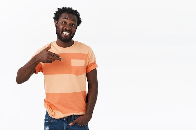 Homem afro-americano bonito e confiante, atrevido, apontando para si mesmo com satisfação