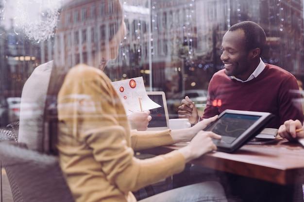 Homem afro-americano bonito e feliz sentado, olhando para a tela e sorrindo
