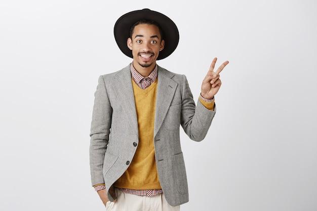 Homem afro-americano bonito e sorridente em terno elegante, mostrando o número dois, fazendo o pedido
