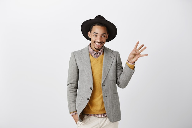Homem afro-americano bonito e sorridente em um terno elegante, mostrando o número quatro, fazendo o pedido
