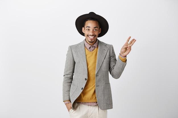 Homem afro-americano bonito e sorridente em um terno elegante, mostrando o número três, fazendo o pedido